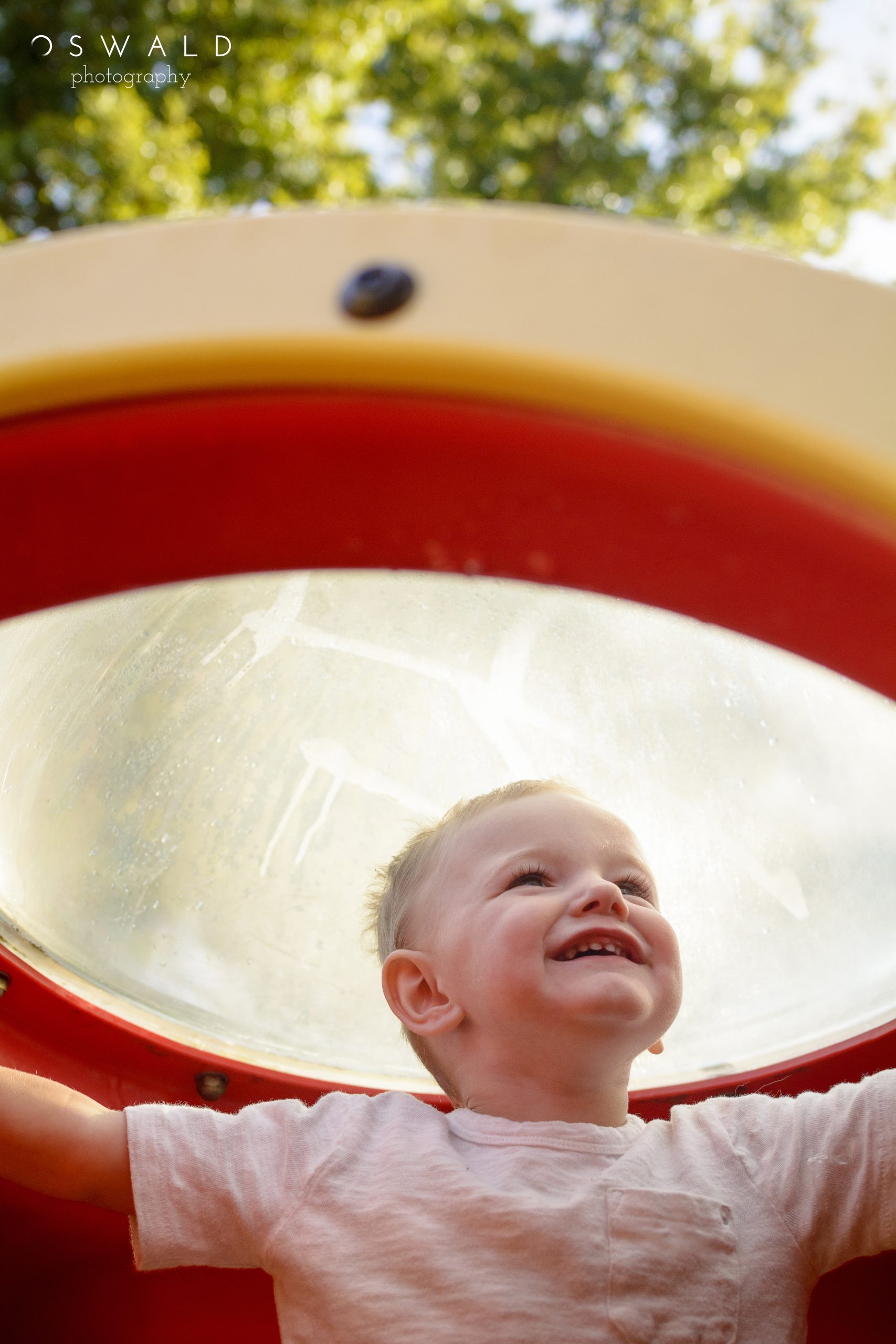 A young boy sits in a playground spaceship, peering out into space.