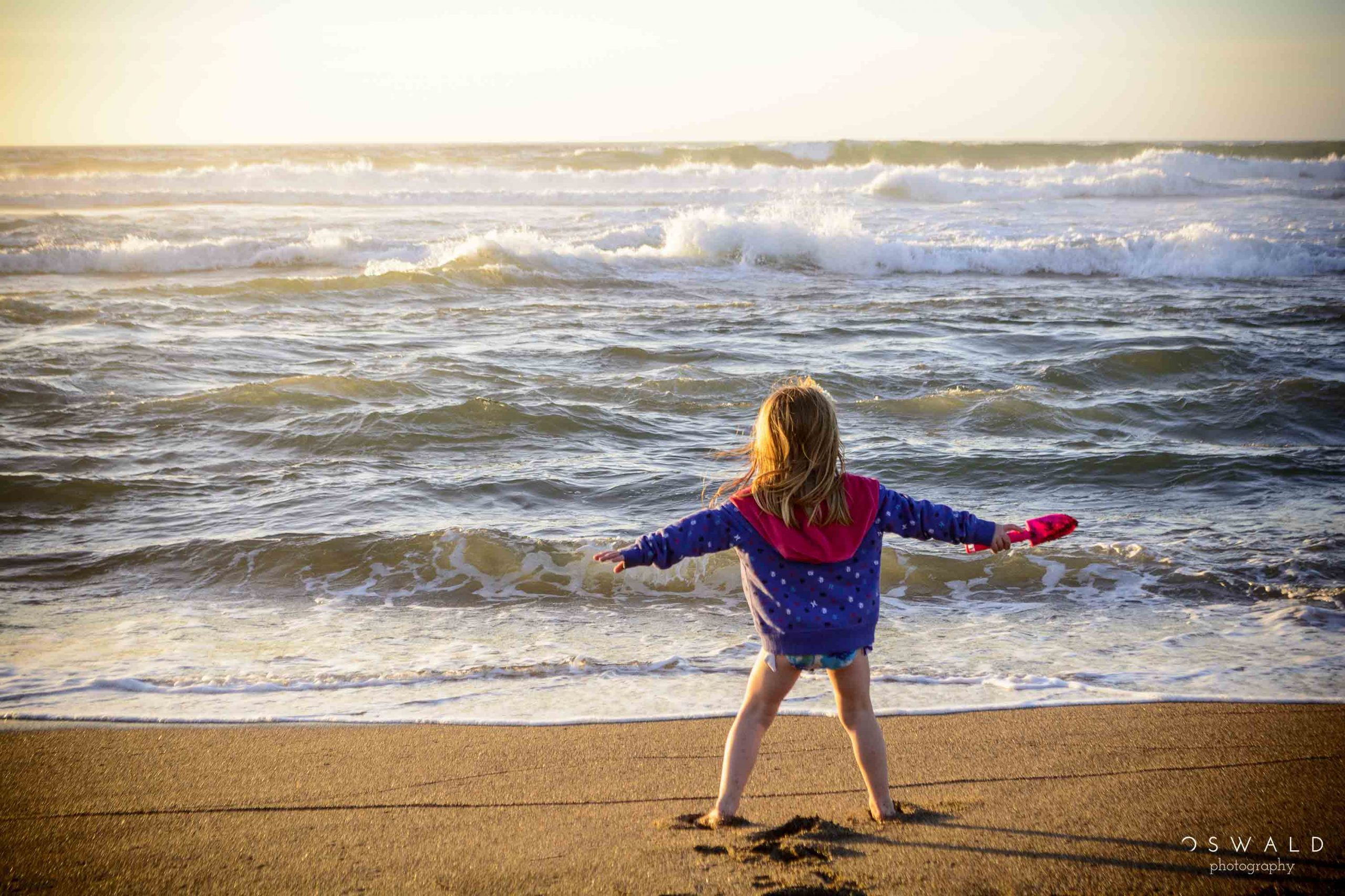 A little girl pretends she can hold back the ocean waves at a Point Reyes Beach