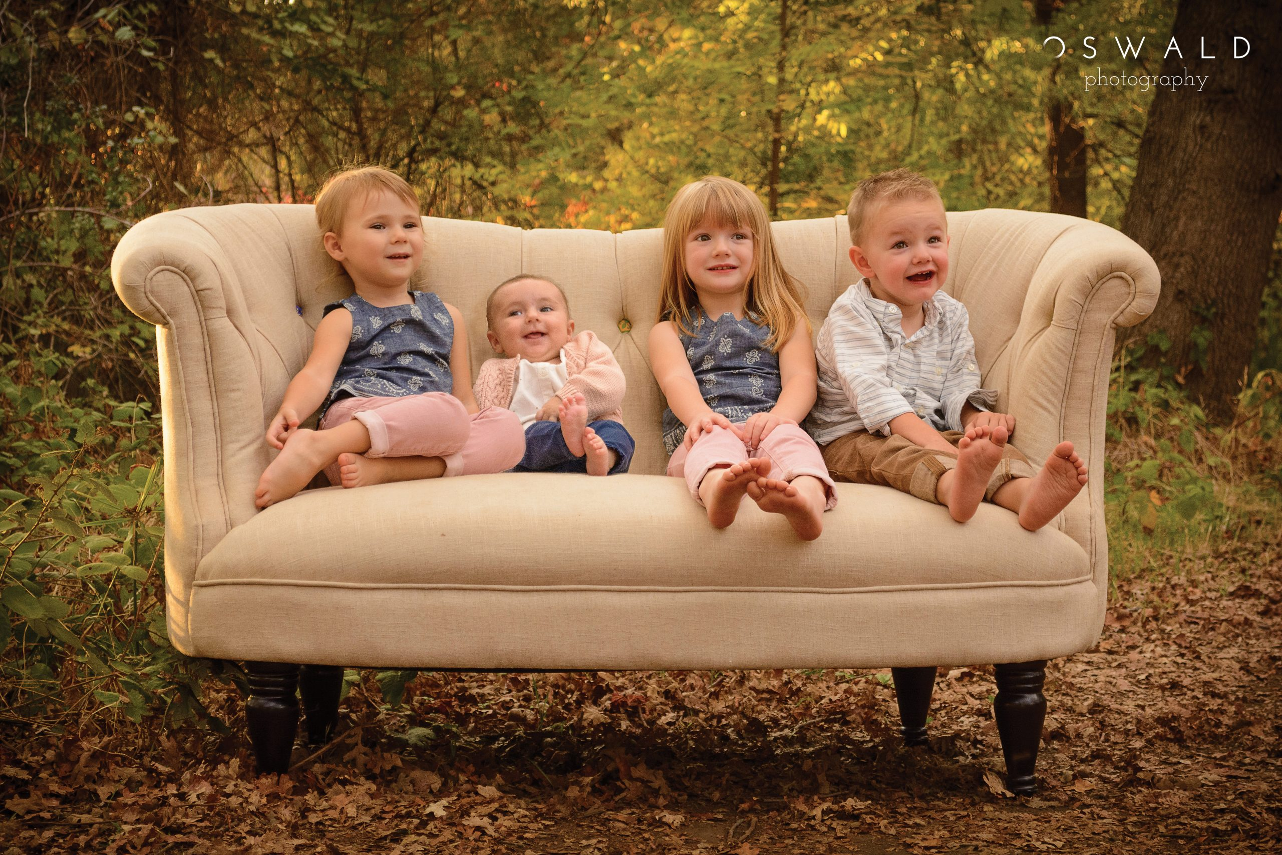 A photo of a group of four barefoot children pose for a portrait on a couch in the woods.