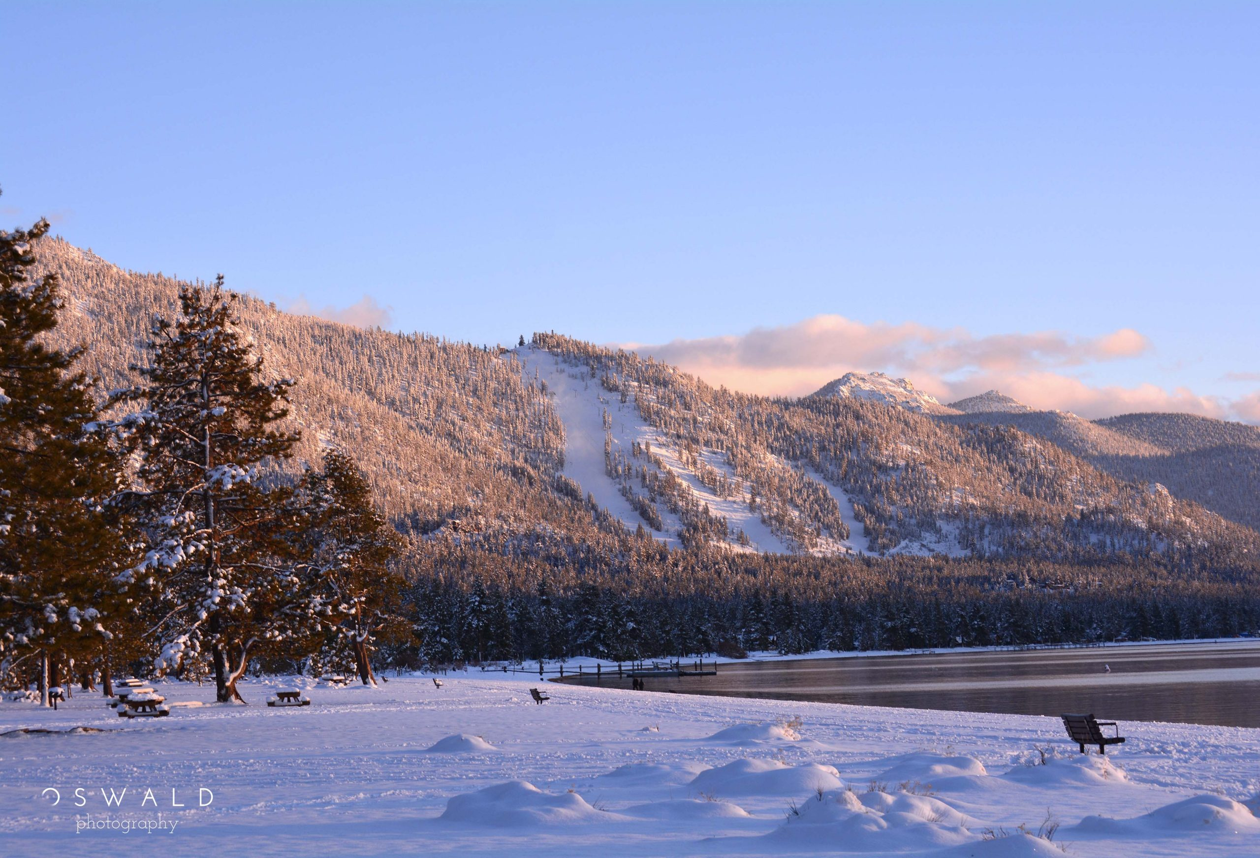 A quiet and lonely photograph of the shores of South Lake Tahoe at Sunset. Recent snowfall blankets the beach as the light begins to wane.