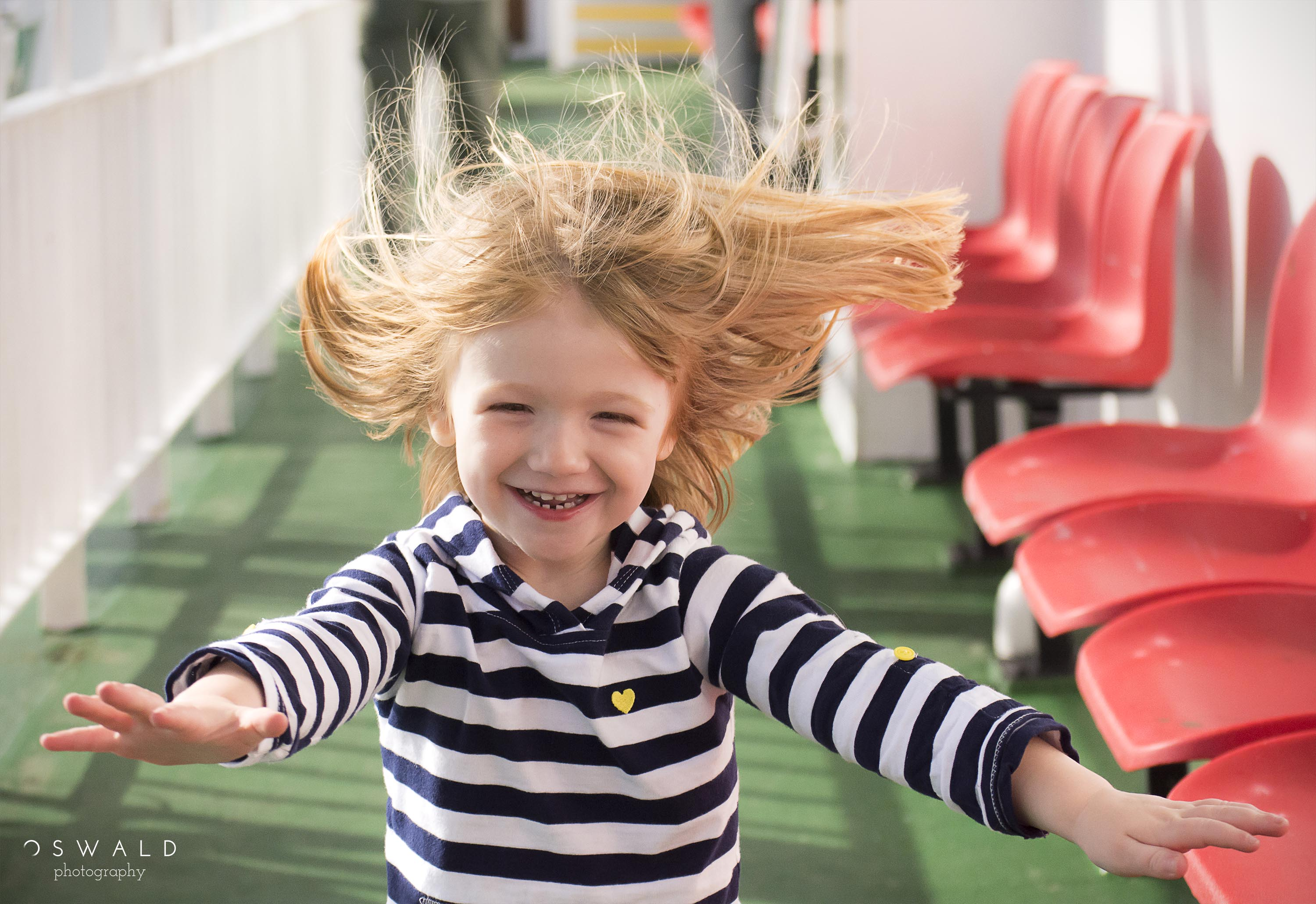 A little blond girl runs smiling down the deck of a ferry boat.