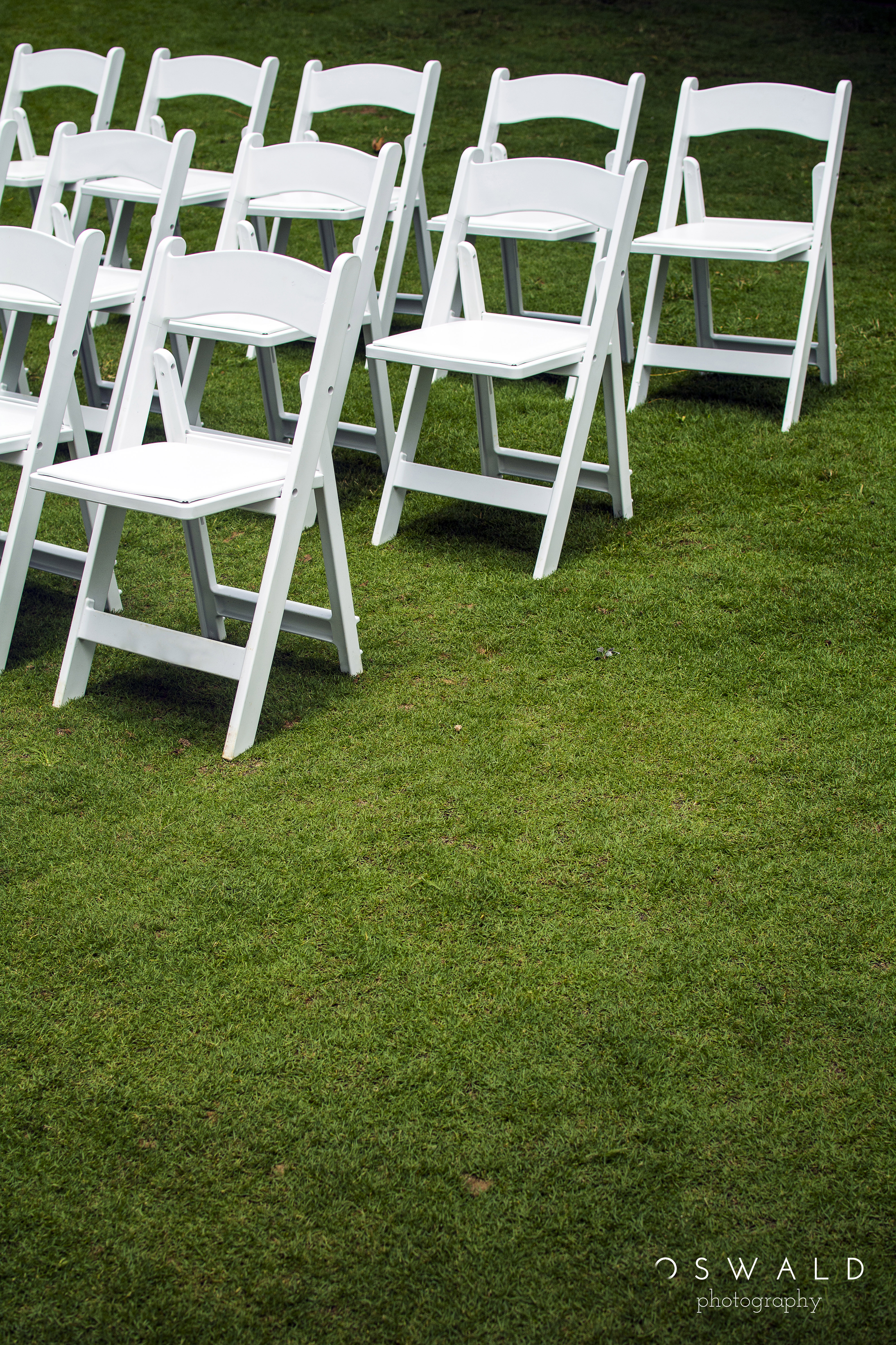 Foldable wedding chairs are set out in a pattern on tropical grass, waiting for wedding guests to arrive.