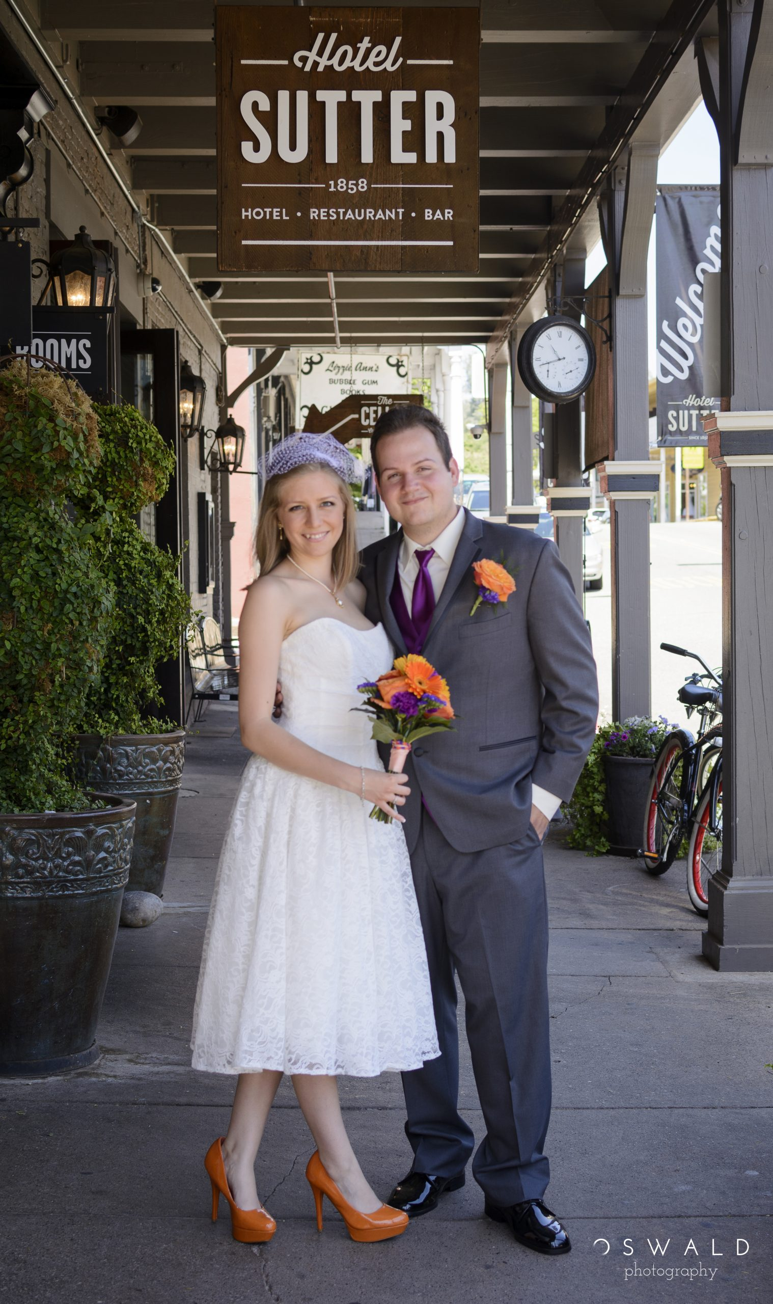 A bride and groom stand on the sidewalk of Old Sutter Creek, California.