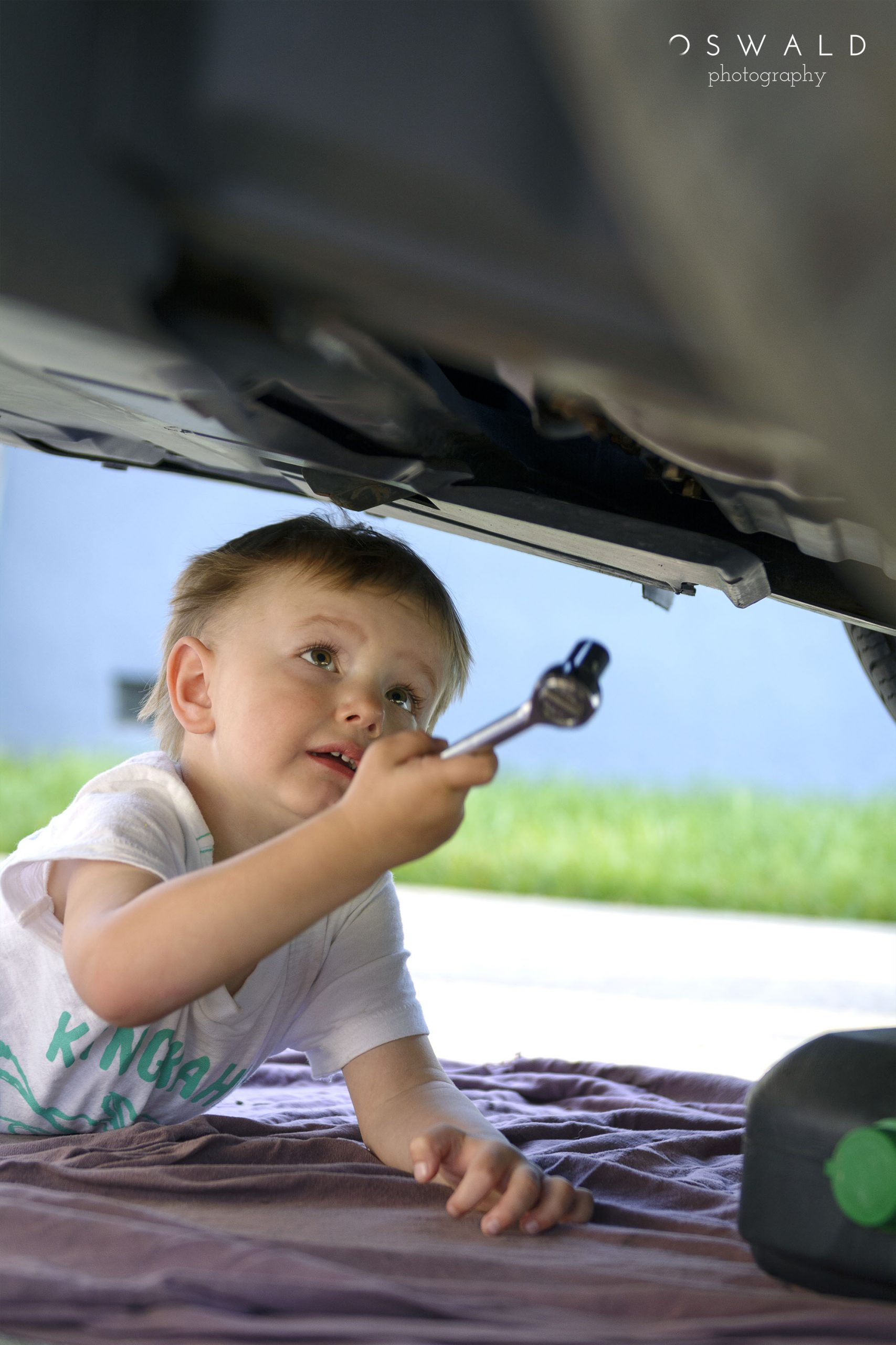 A photograph of a young caucasian boy holds a socket wrench under a car with ambitious plans for repairs.