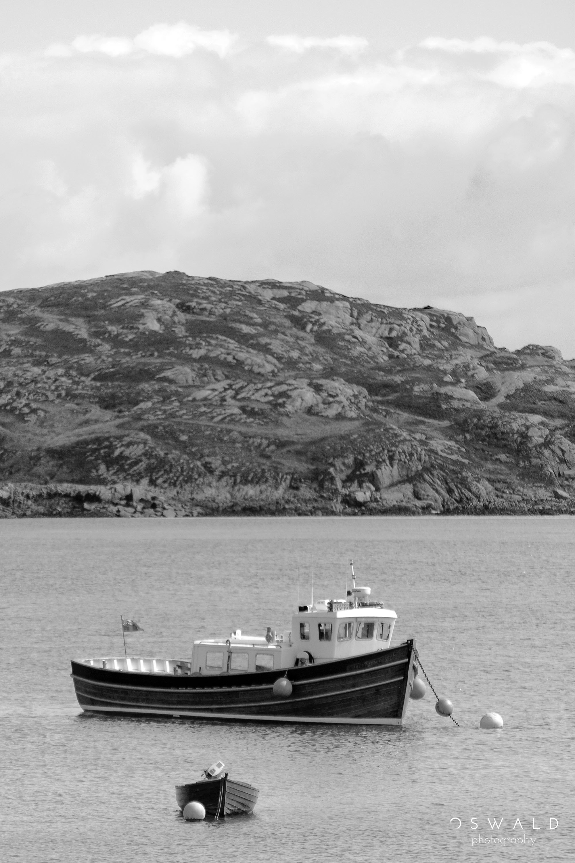 A monochrome photo of a boat and its dinghy floating in calm waters between the coast of Mull and Iona in Scotland.