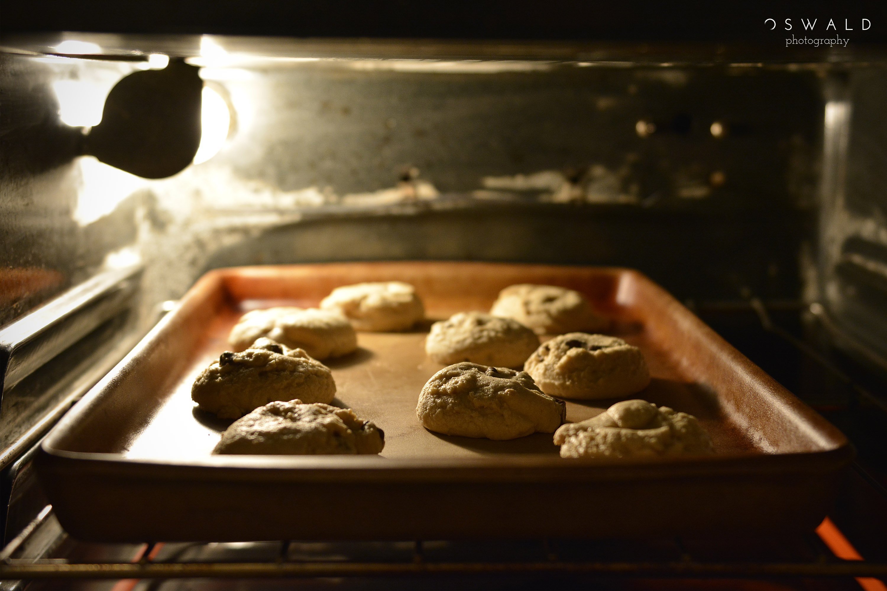 A photograph of chocolate chip cookies on a baking sheet baking inside an oven