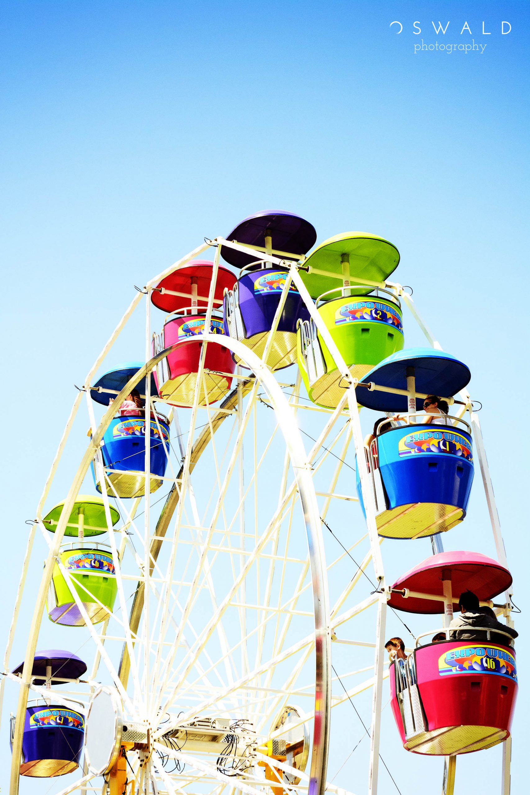 A hard-lit photograph of a ferris wheel in motion at the Elk Grove Western Festival on a spring afternoon.