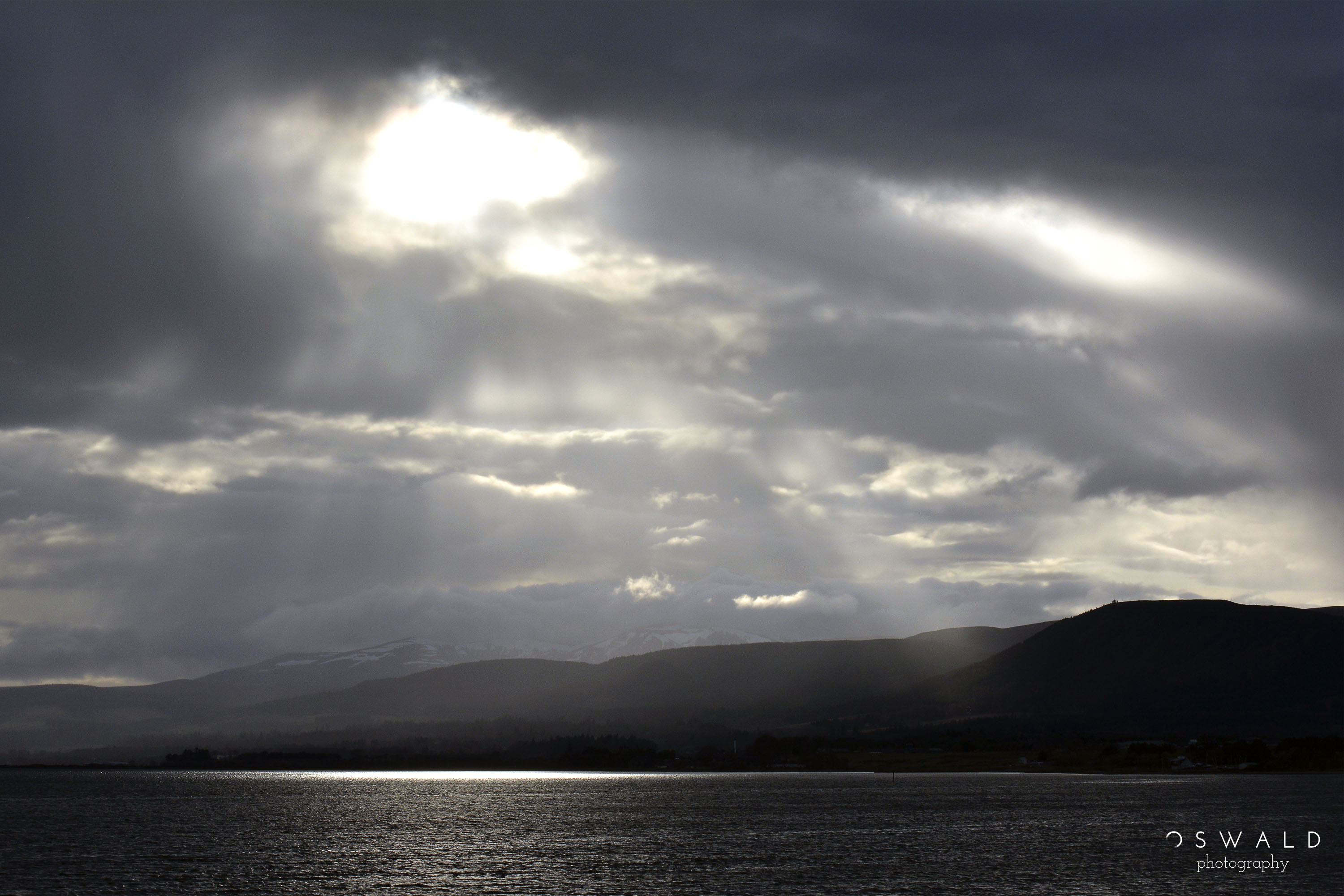 Rays of sun shoot through the afternoon clouds that cover Alness Bay in Scotland.