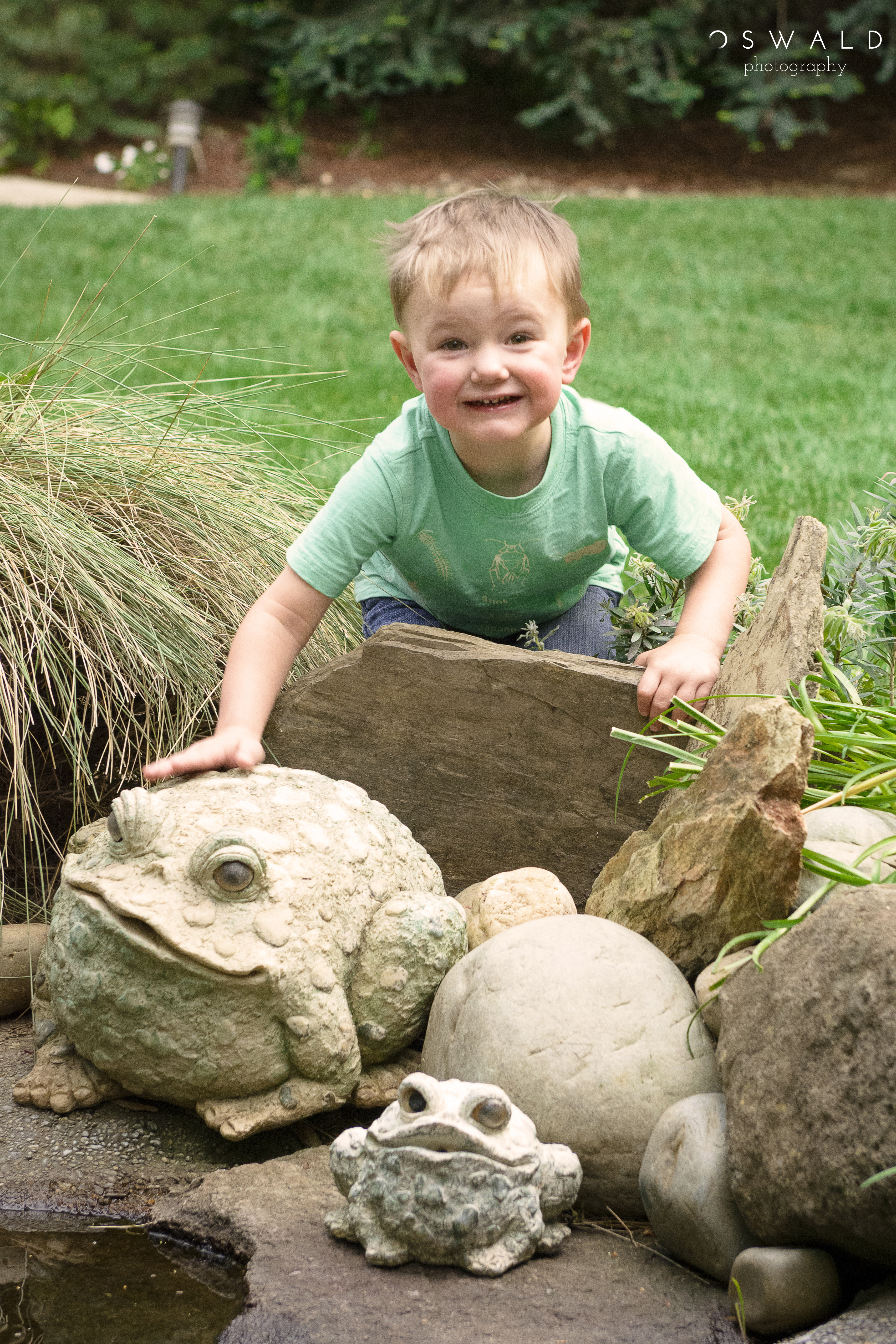 Photograph of a little caucasian boy petting a decorative stone toad by the side of a backyard pond.
