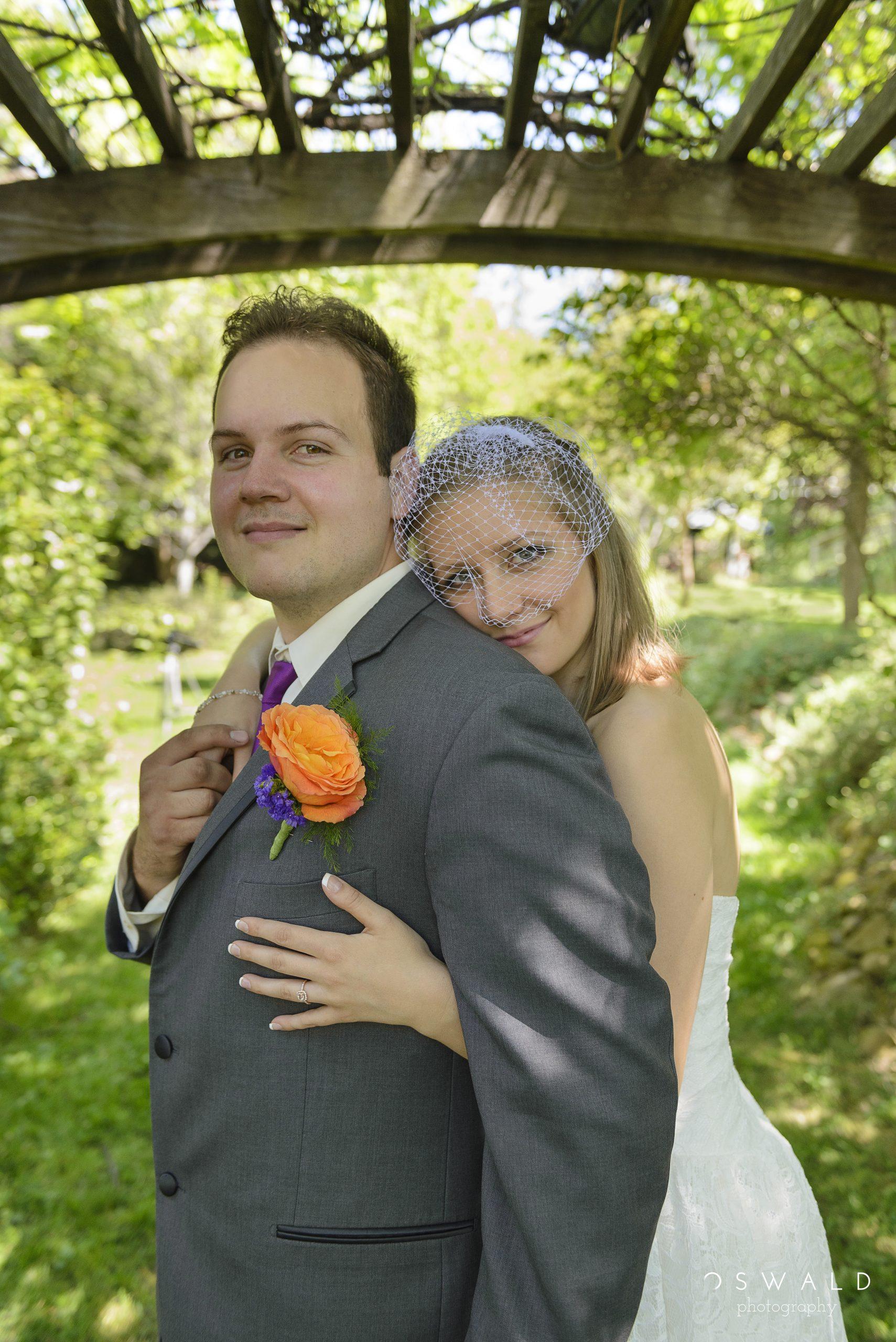 Photograph of groom and his veiled bride underneath a trellis.