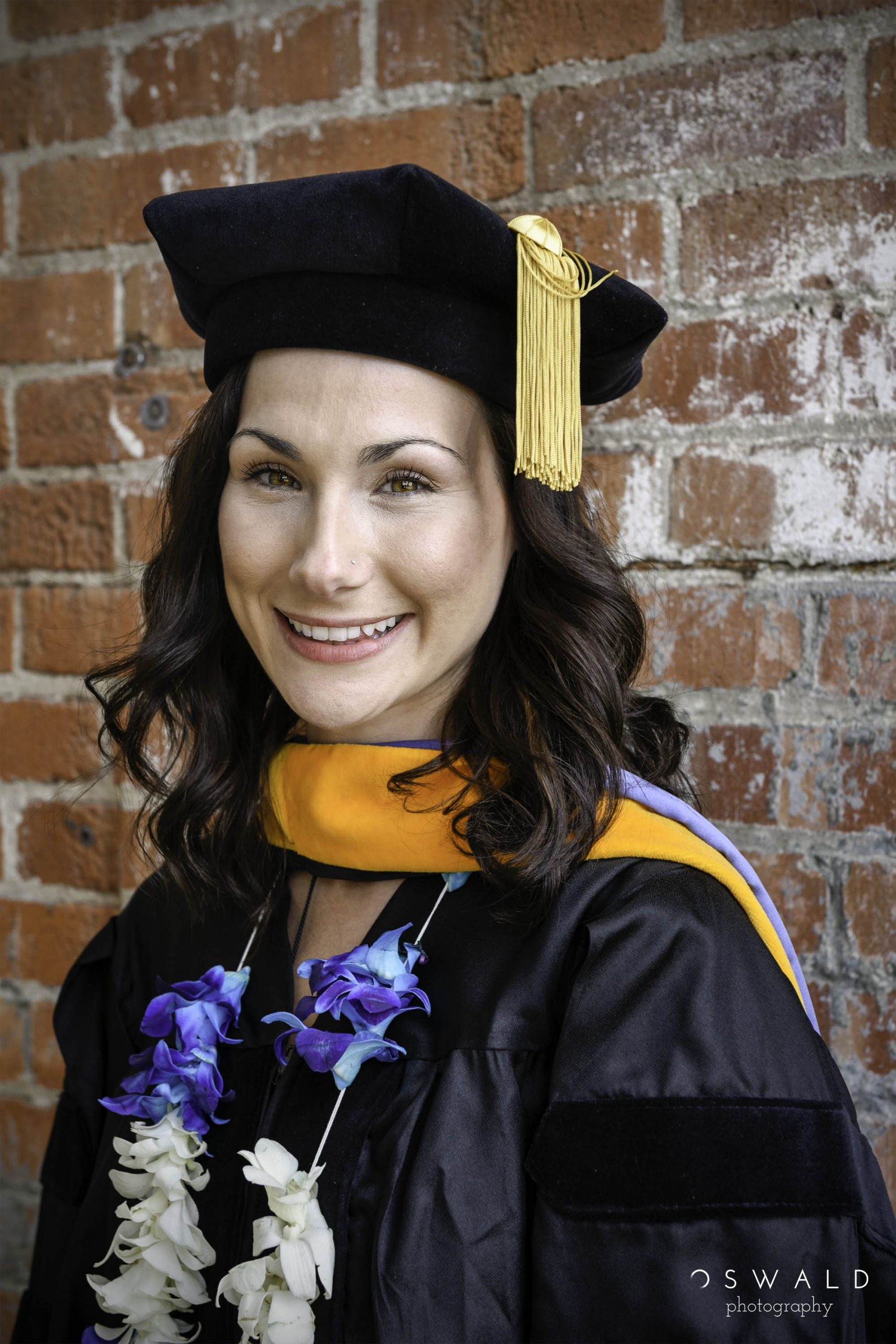 A portrait photograph of a young, caucasian female doctoral graduate on her graduation day wearing a tam o' shanter.