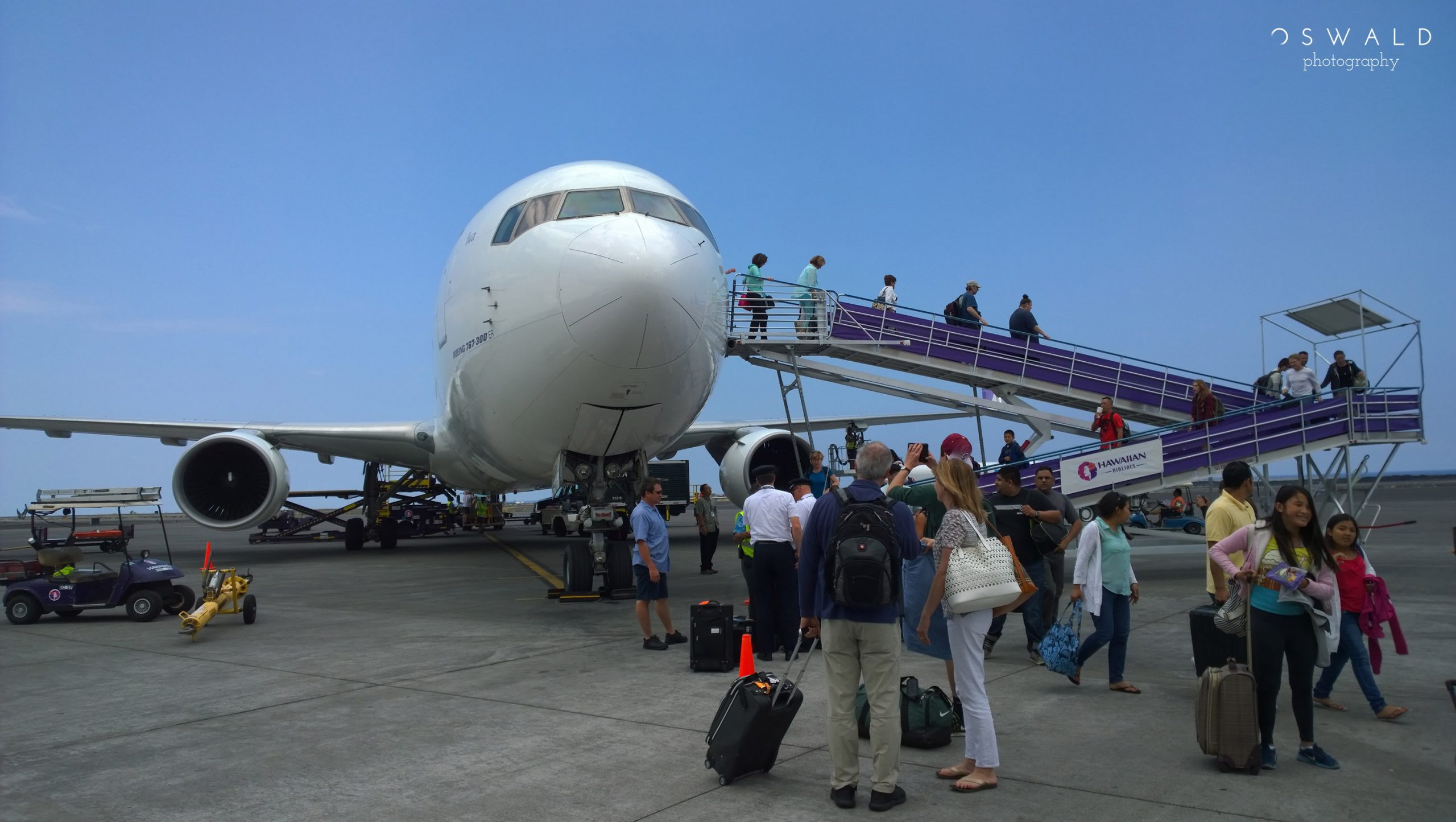 A landscape photograph of passengers unloading from an airplane on a small airport runway.