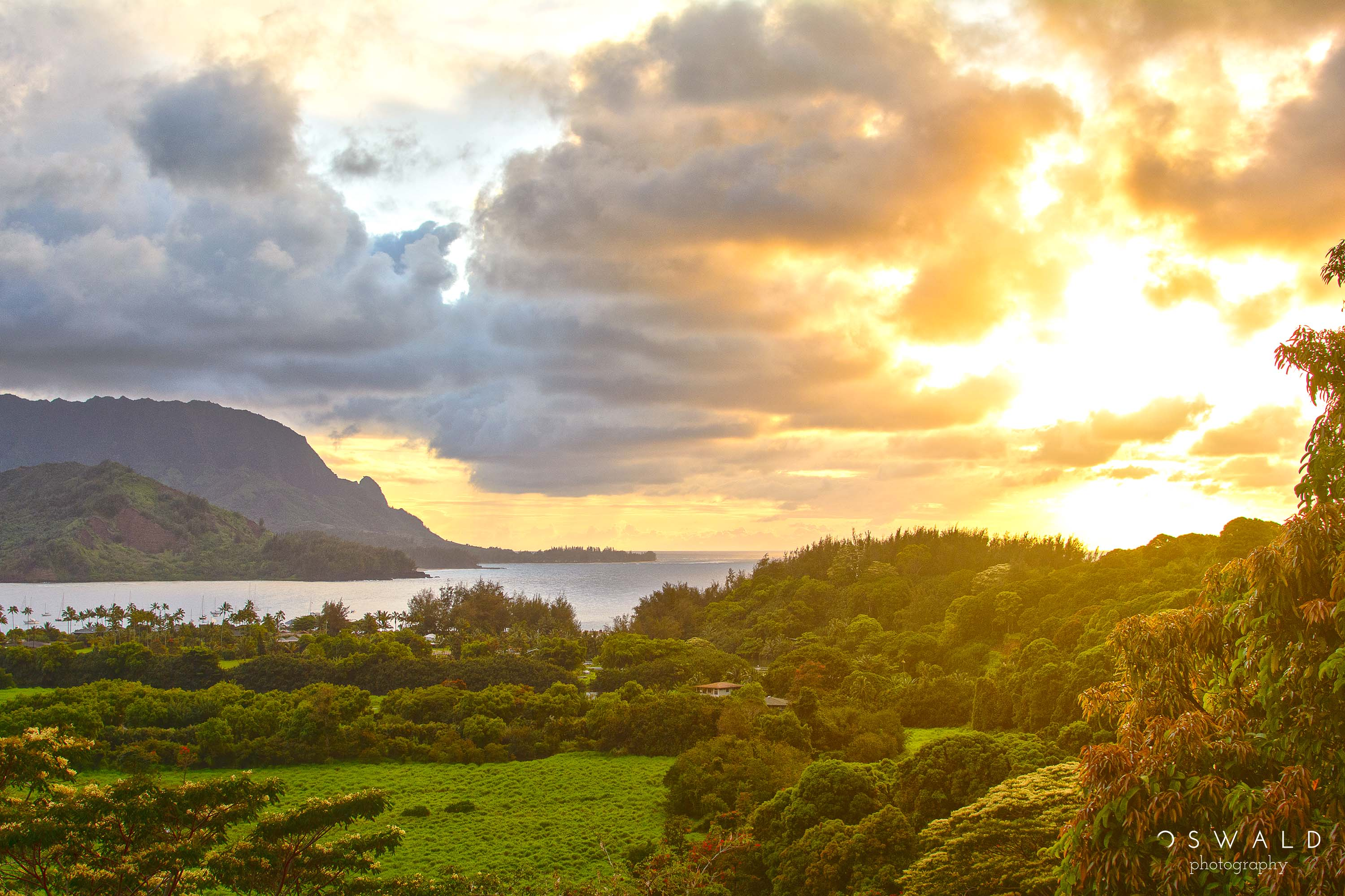 HDR landscape photograph of a dramatic and cloudy sunset over Hanalei Bay in Kauai.