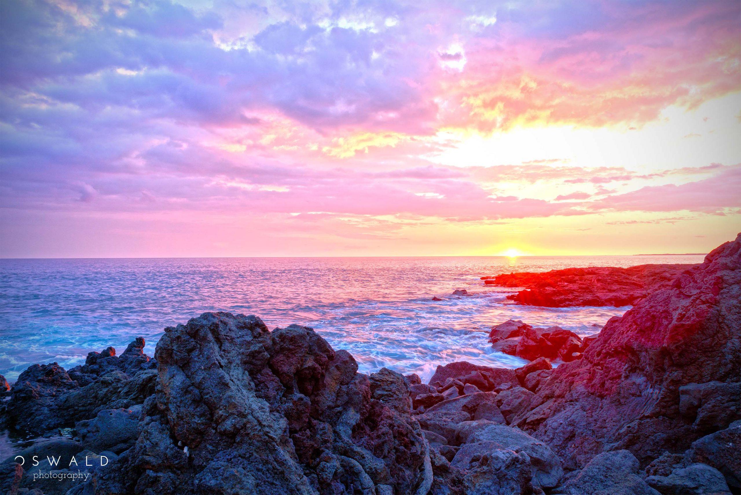 A sunset photograph of a rocky shore along the coast of Kona on the Big Island of Hawaii.