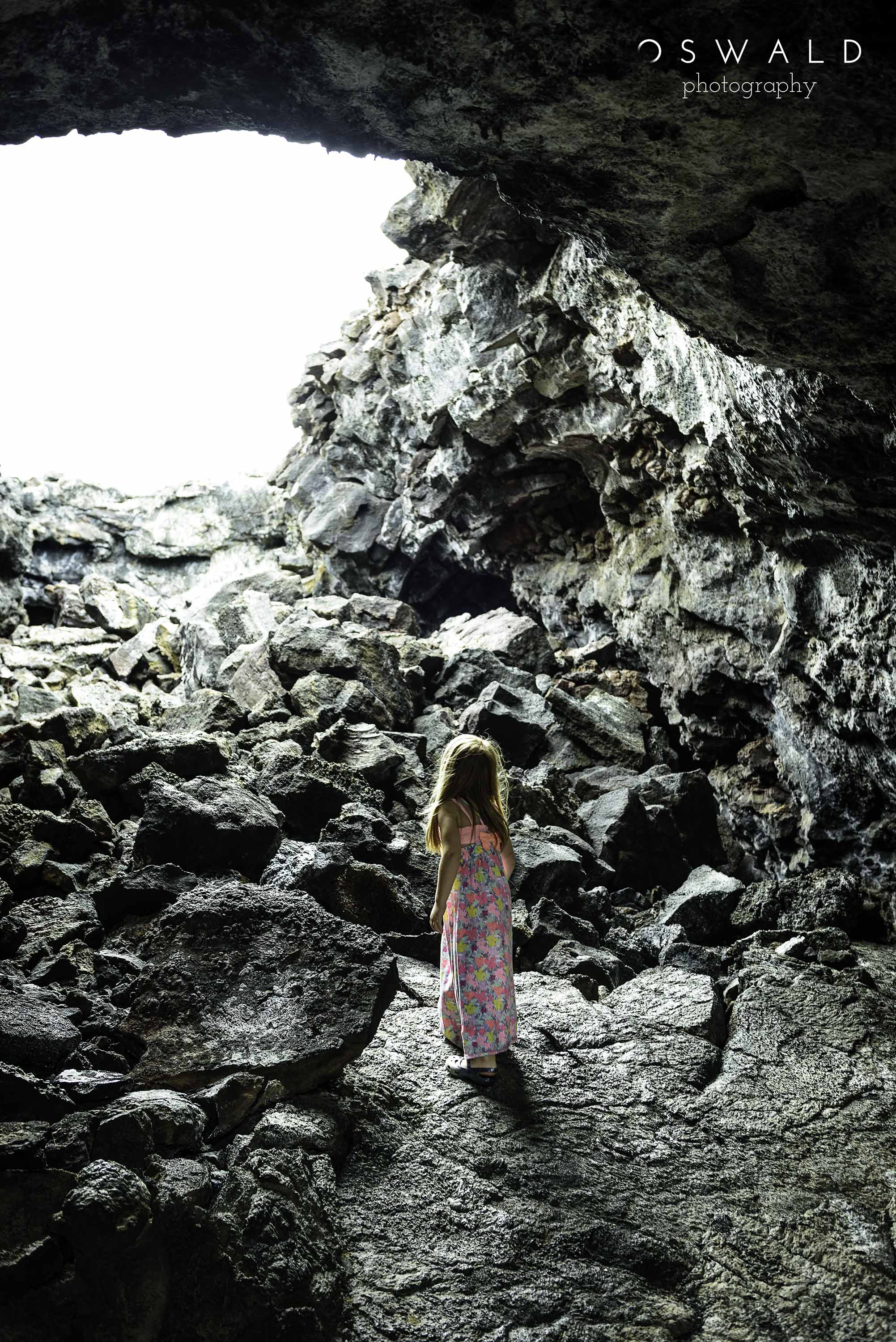 A little girl in a colorful dress looks up and out of the mouth of a lava tube near Kona, Hawaii.