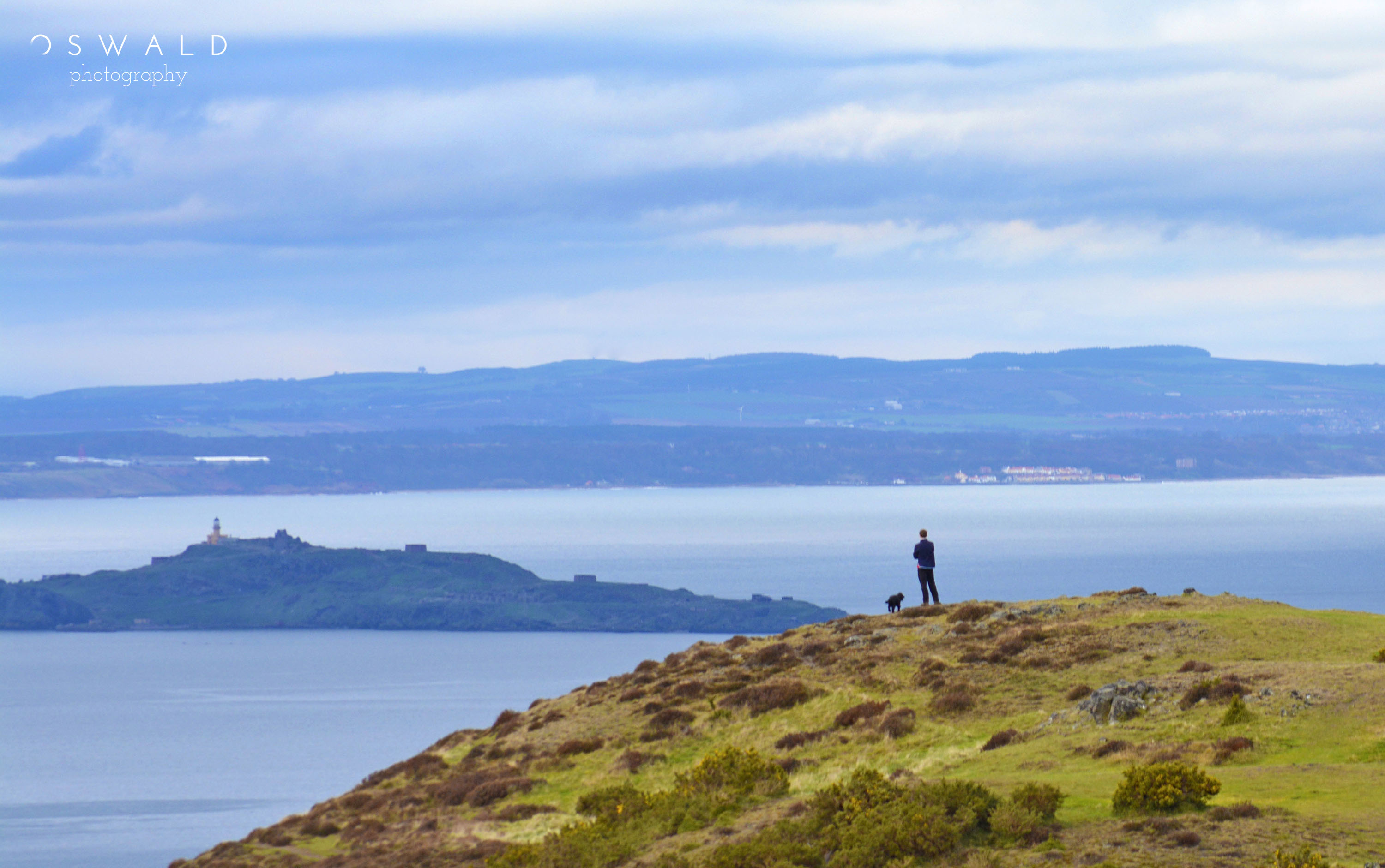 A man and his dog stand atop Arthur's Seat in Edinburgh, Scotland, overlooking the Firth of Forth as dramatic clouds roll in.