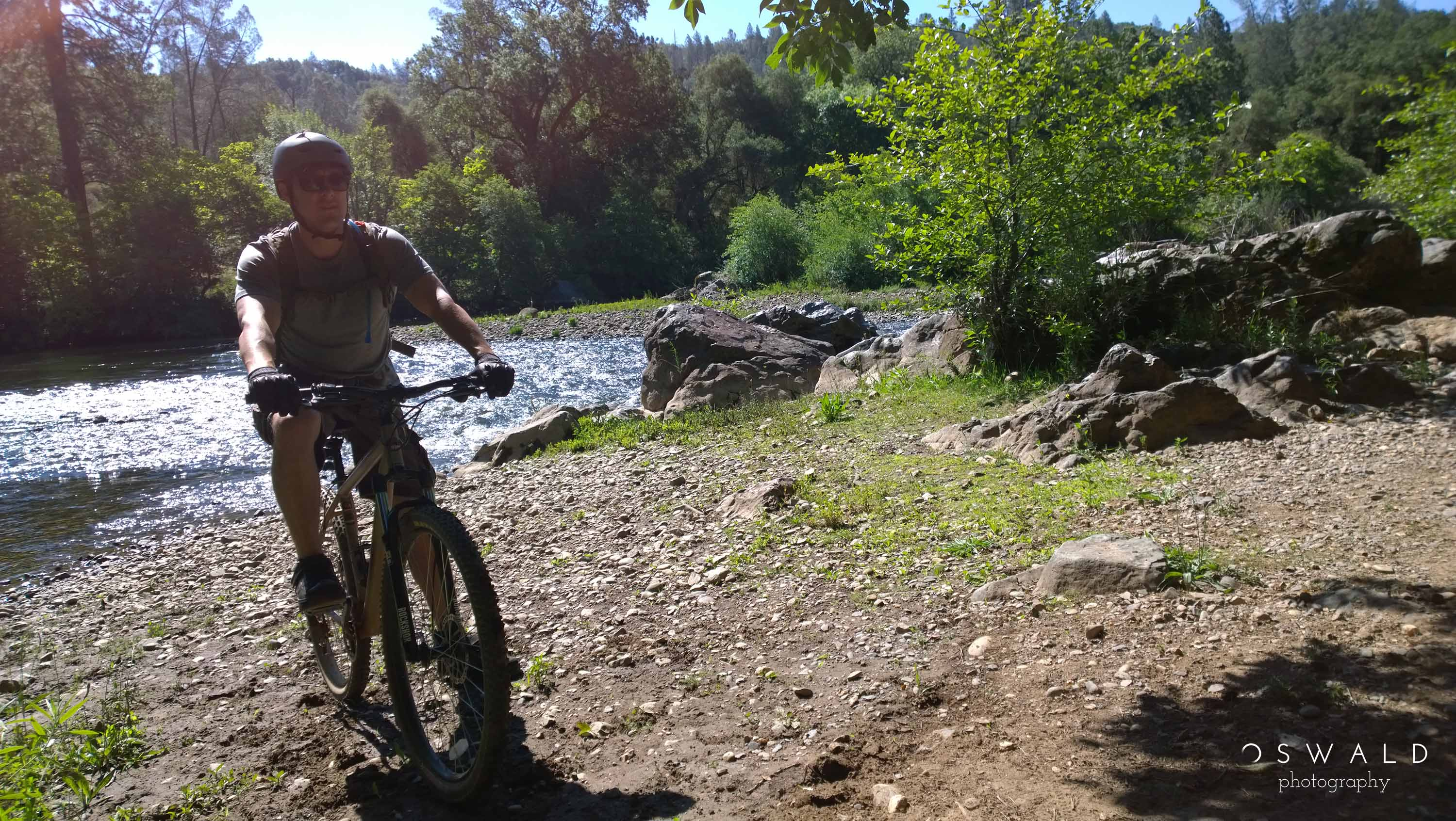 Photograph of a mountain biker riding along the shores of the South Fork of the American River.