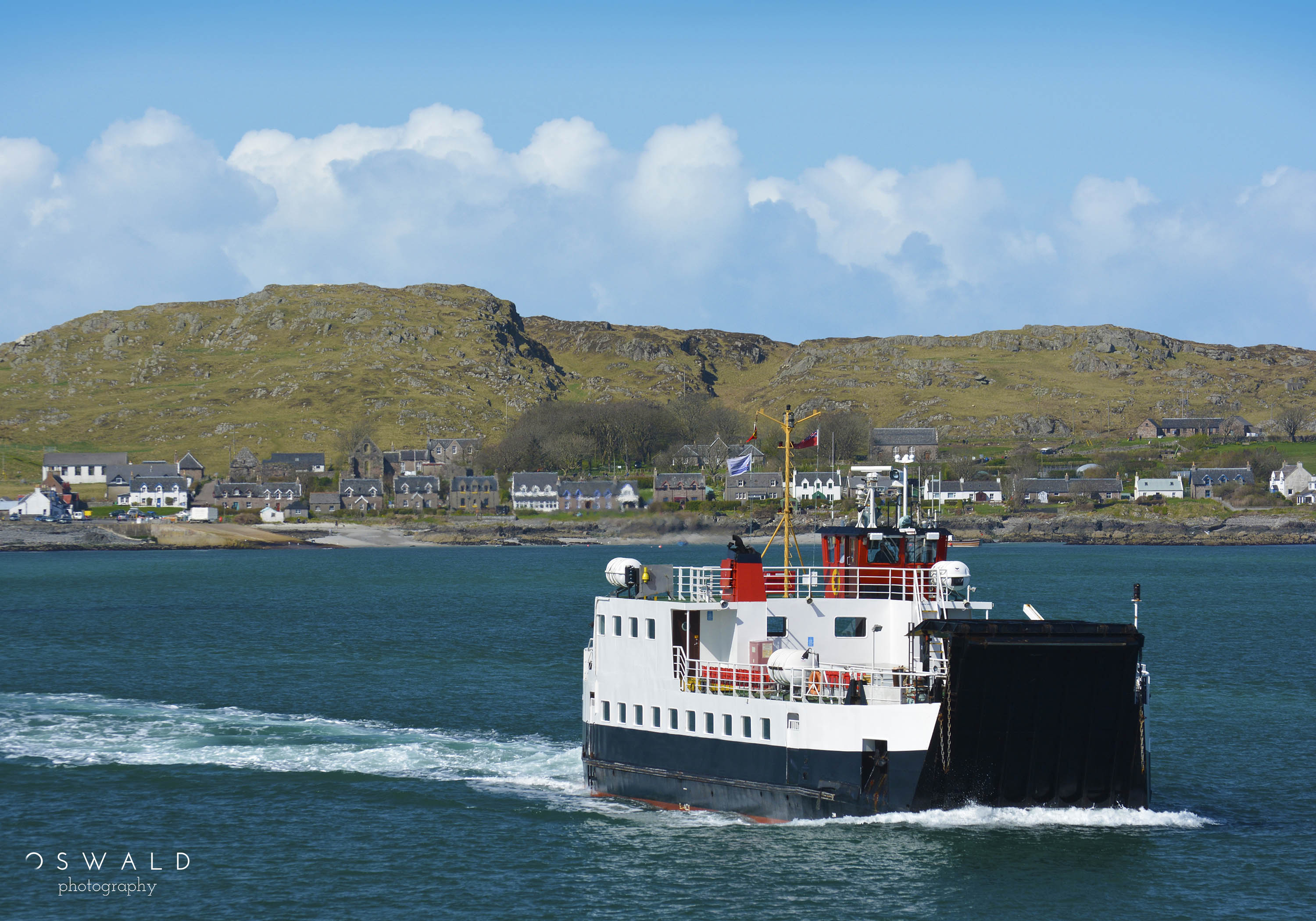 A CalMac ferry boat returns from the Isle of Iona to the Isle of Mull in Scotland over gorgeous blue waters.