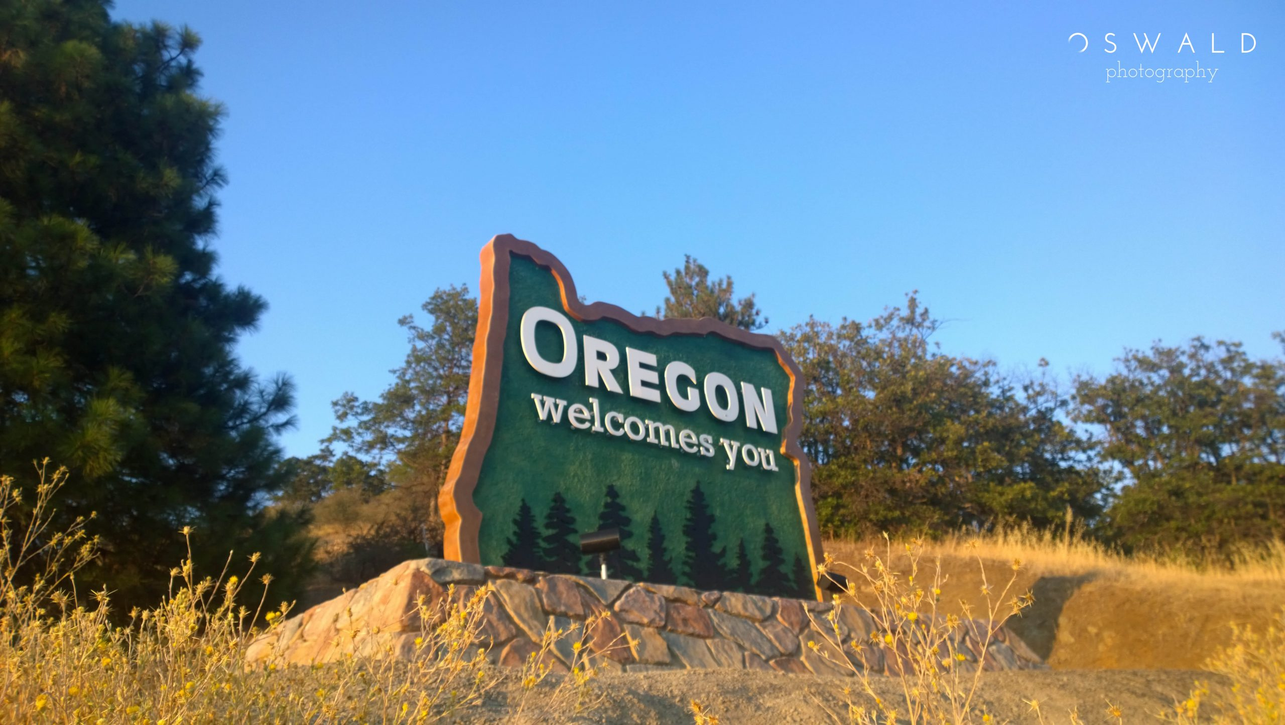 "Photography of a sign that reads ""Oregone welcomes you"" at the Oregon-California border."