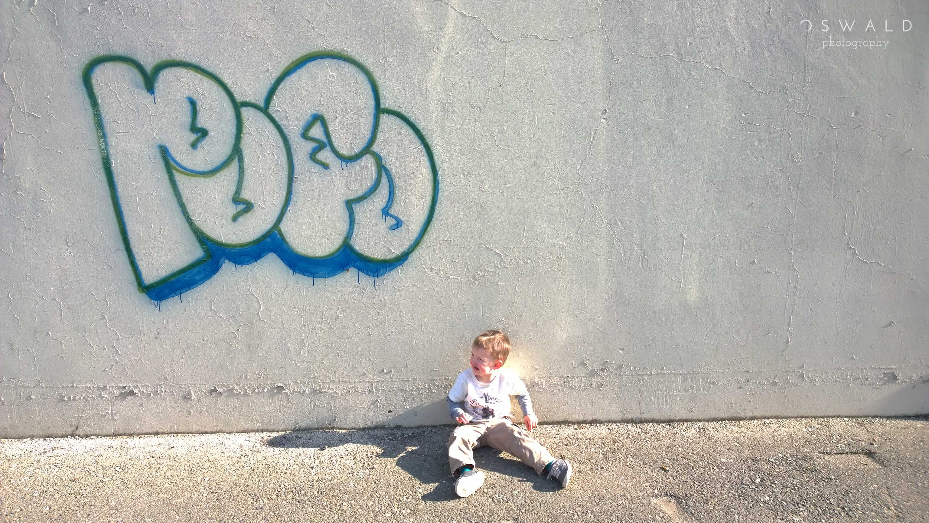 A little boy sits in front of a wall tagged with graffiti.