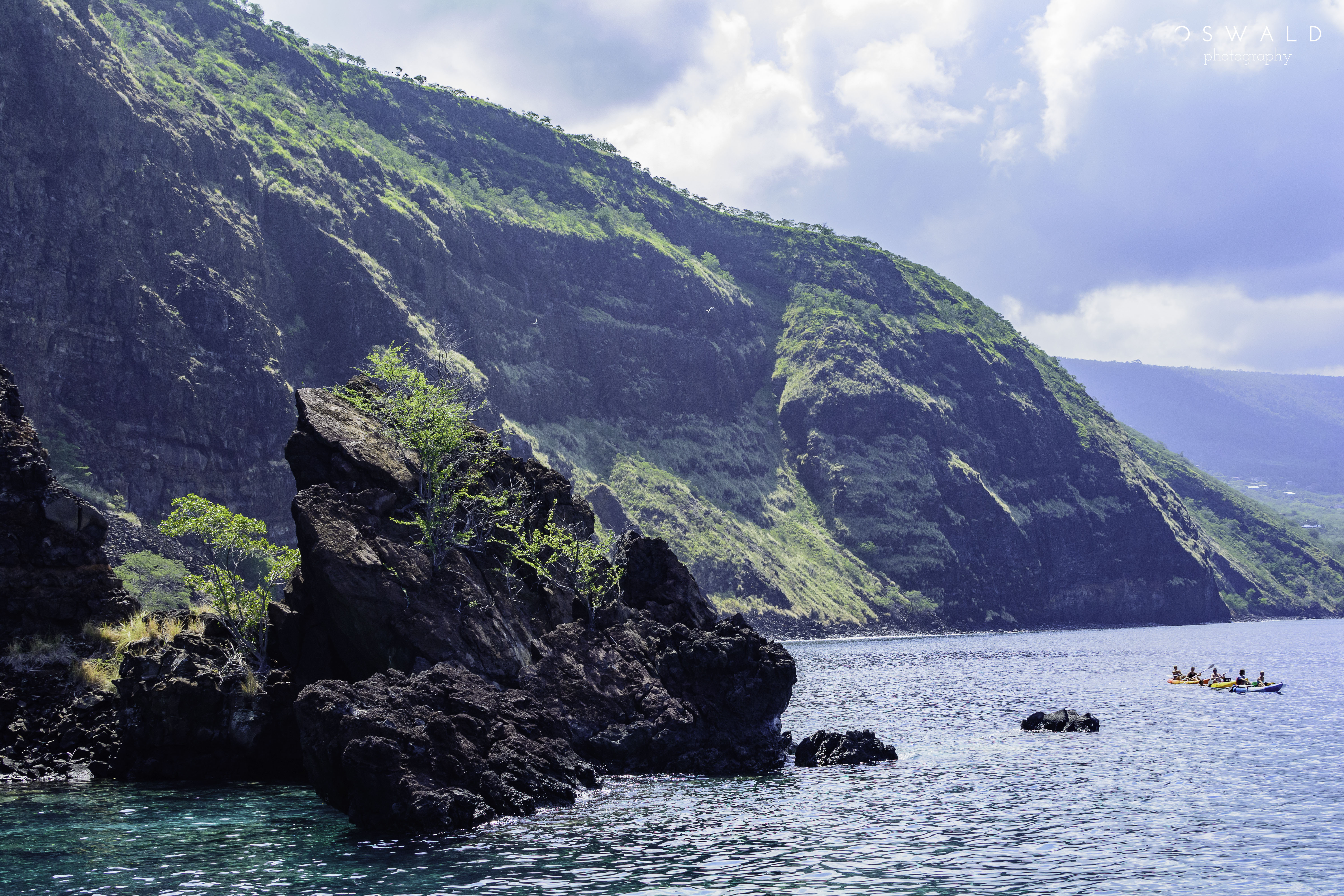 A vivid landscape photo of the hills and shores of Hawaii's Kealakekua Bay, taken from a snorkel tour boat out upon the water.