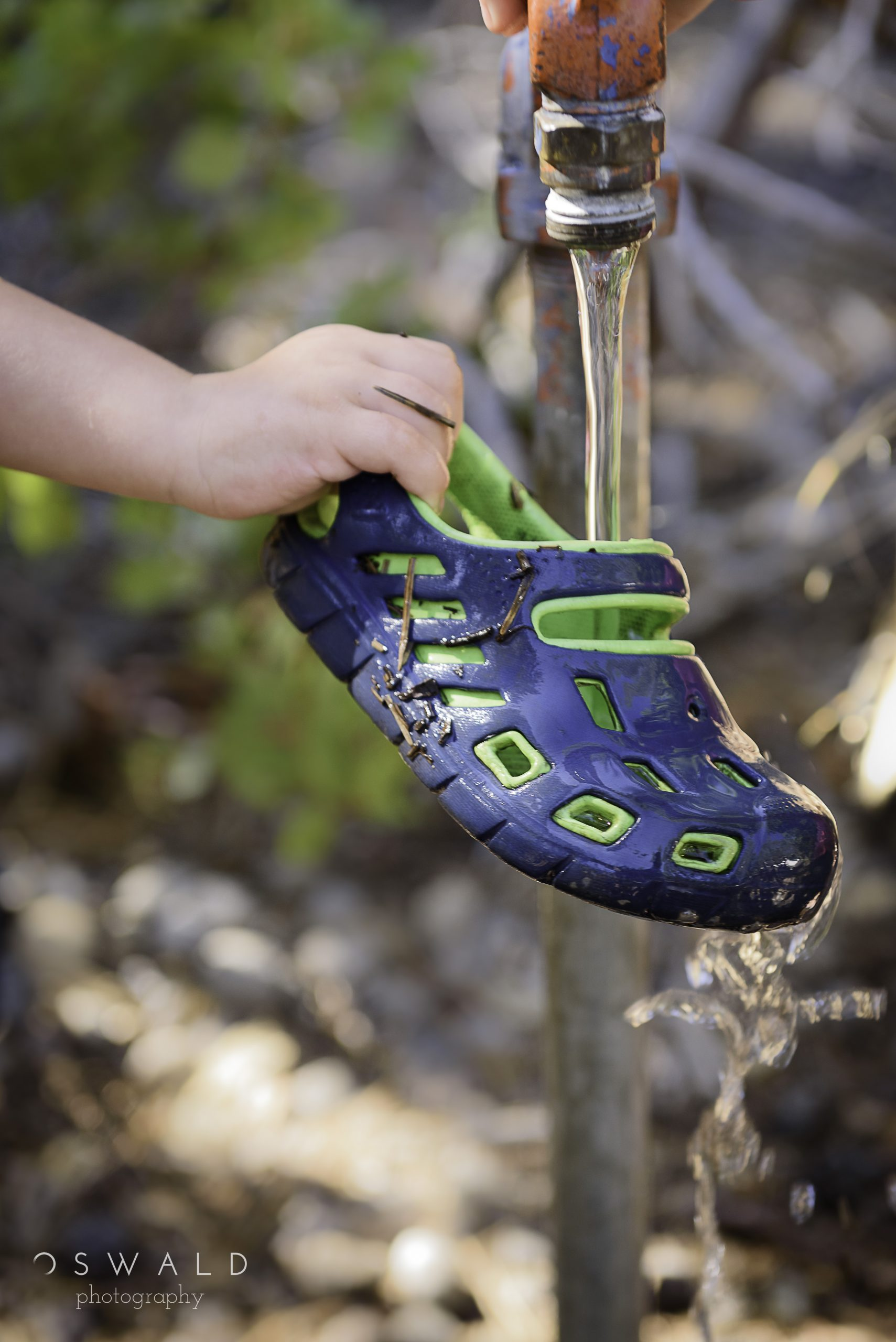 Photograph of water flowing over a child's shoe.