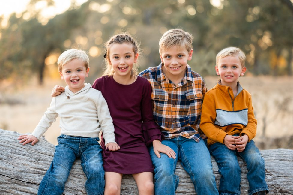 A sister and her three brothers pose for a portrait at the American River Parkway
