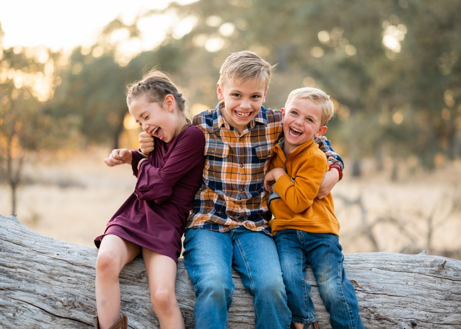 A brother tickles his brother and sister during portraits at the American River Parkway