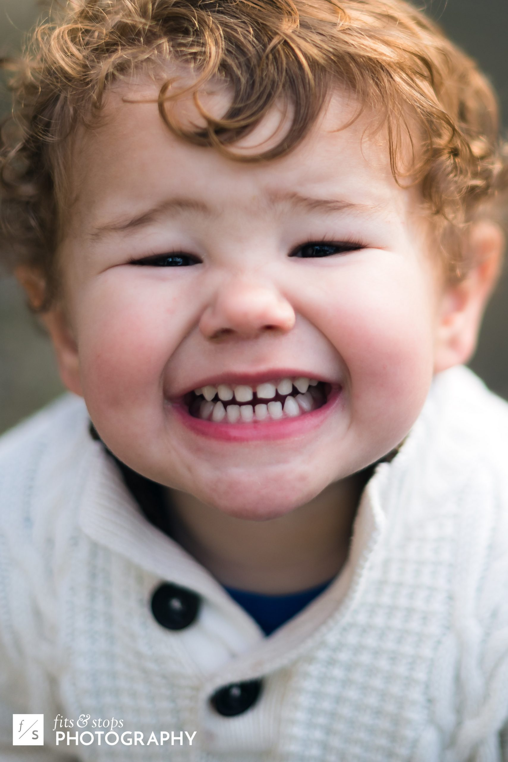 A close up portrait photograph of a young caucasian boy with a contagious smile, with very shallow depth of field.