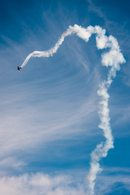 Photograph of a biplane leaving a squiggly trail of smoke at San Francisco's Fleet Week