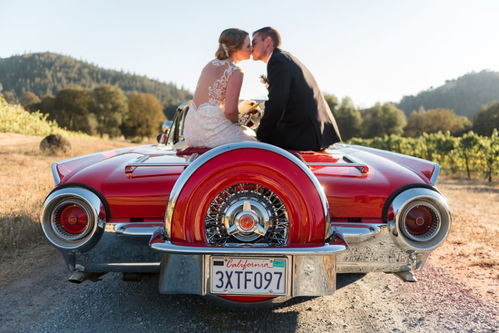 A bride and groom kiss atop a vintage Ford Thunderbird.
