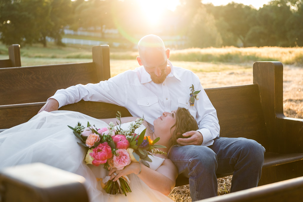 A bride lays her head in her groom's lap while on wooden pews at a country wedding.