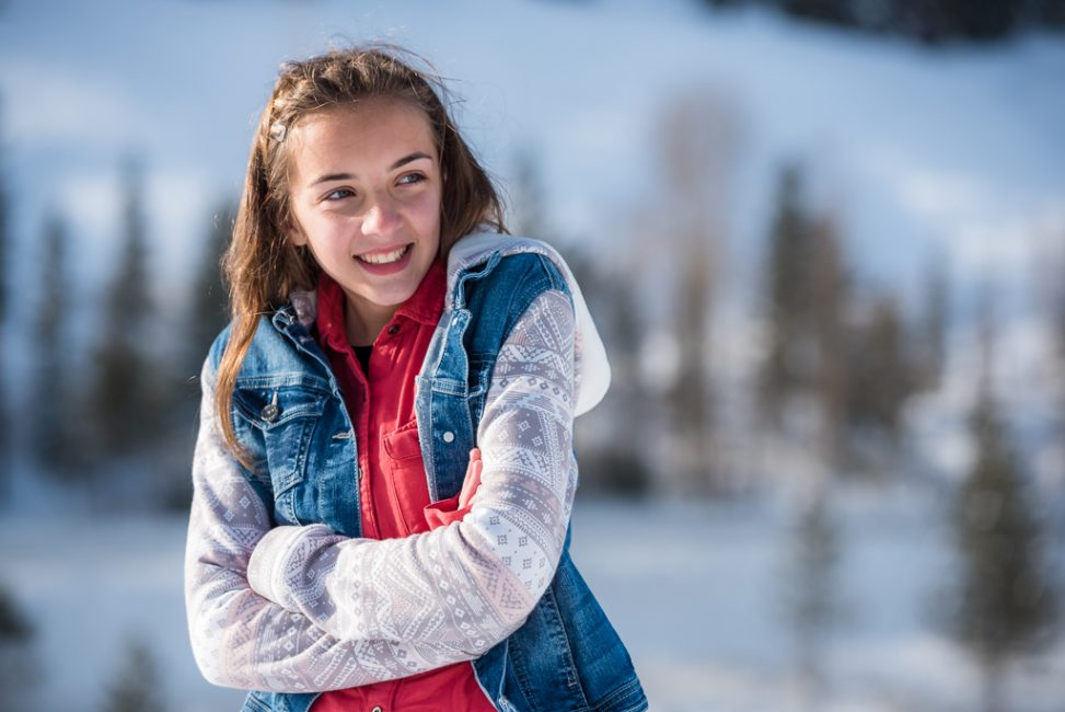 A young teenage girl poses for a portrait in the snow