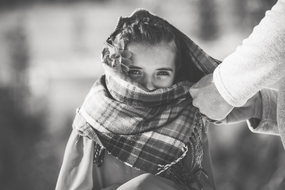 Black and white portrait of a young girl wrapped in a scarf in the snow