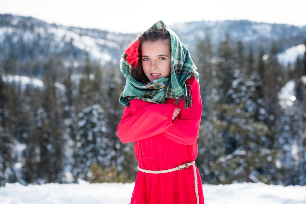 Portrait of a young girl wrapped in a scarf in the snow