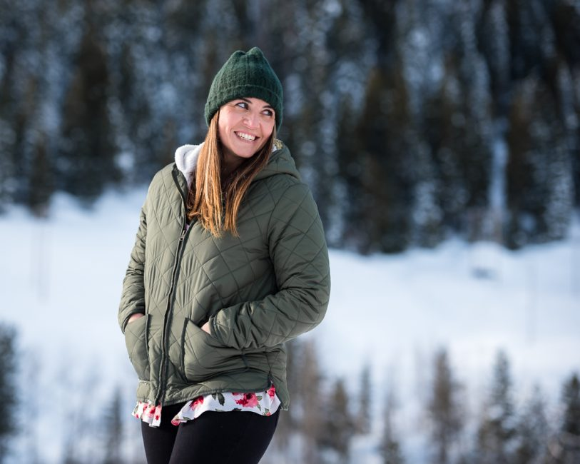 A young woman in a beanie stands for a portrait in the snow at the Loch Leven Trailhead.
