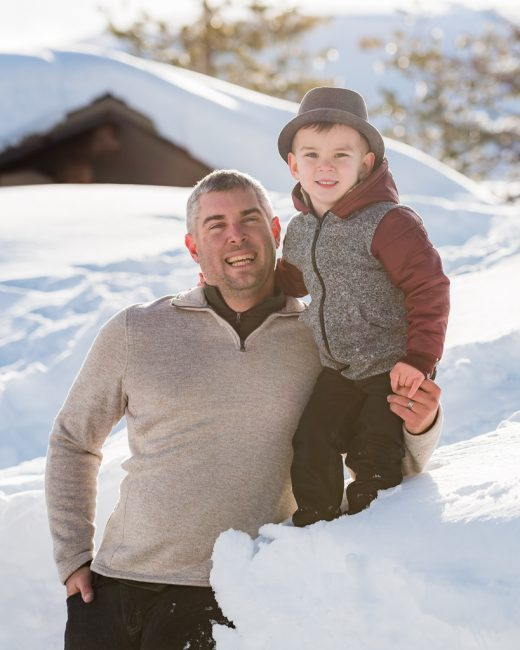 A father and son pose for a portrait in the snow.