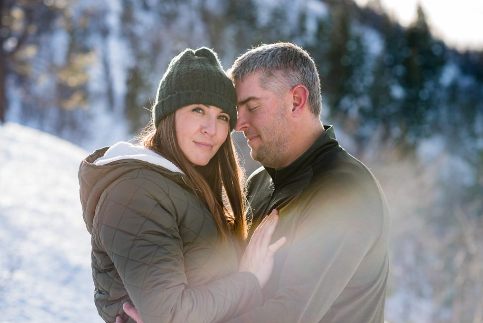 an intimate portrait of a couple standing in the snow.