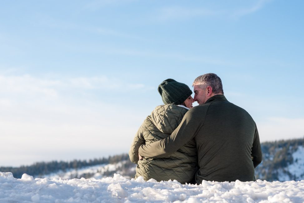 Portrait of a couple seated on the snow in the mountains at Emmigrant Gap, CA.