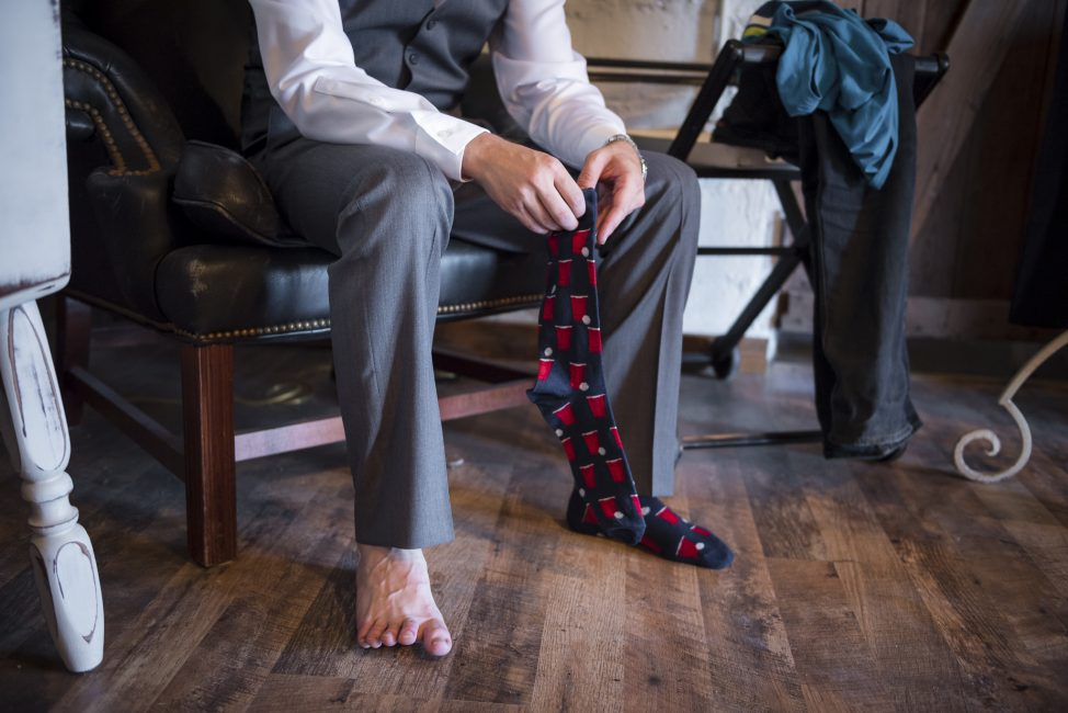 A groom puts on his beer pong-themed socks while getting ready for his wedding ceremony.