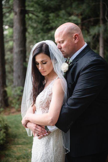 A groom nuzzles his new bride after their Forest House Lodge wedding ceremony