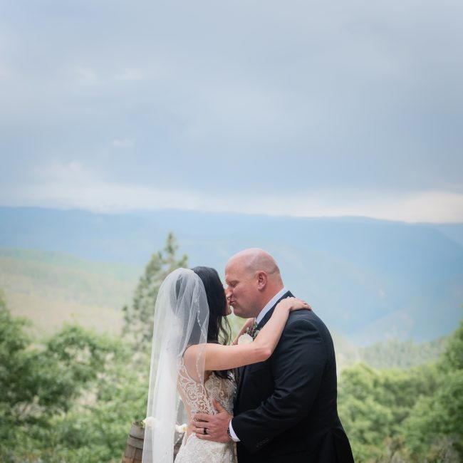 A bride and groom kiss during their Forest House Lodge Wedding