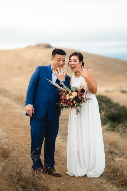 An Asian American bride and groom show of their wedding rings in Fremont, CA.