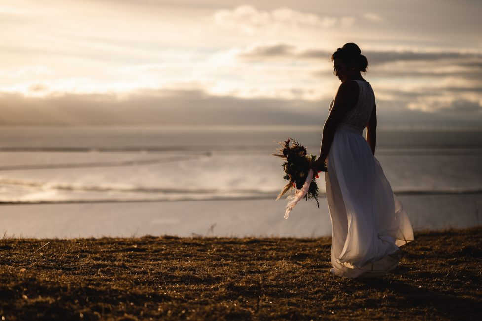 Silhouette of a bride holding a bouquet while looking out over the San Francisco Bay.