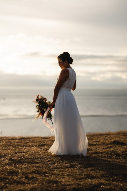 A bride clutches her bouquet on a windy day, overlooking the San Francisco Bay.