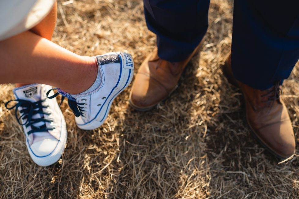 A bride wears Converse All Star shoes customized with her and her groom's initials.