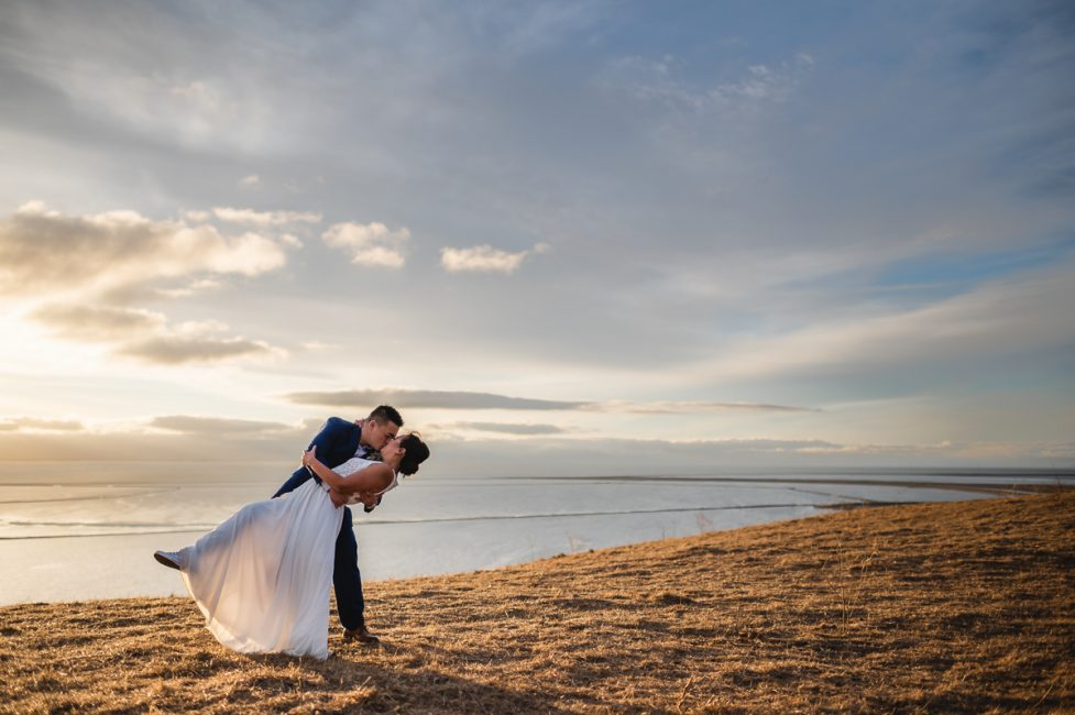 A groom dips his bride while overlooking the San Francisco Bay.