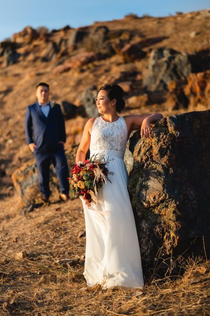 Romantic photo of a groom looking on at his bride during sunset on a rocky hill.