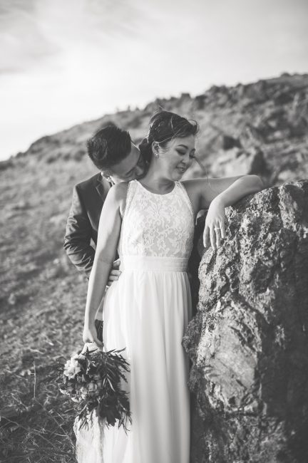 Black and white photo of a groom kissing his bride's neck at Coyote Hills Regional Park.