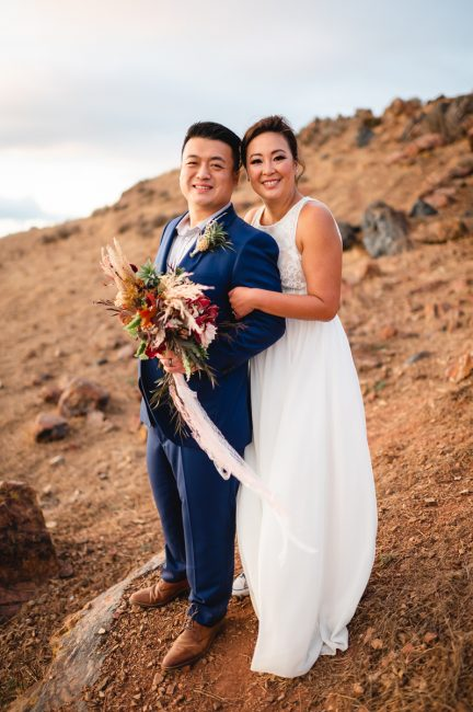 Newlyweds hold each other on a hill at Fremont's Coyote Hills Regional Park